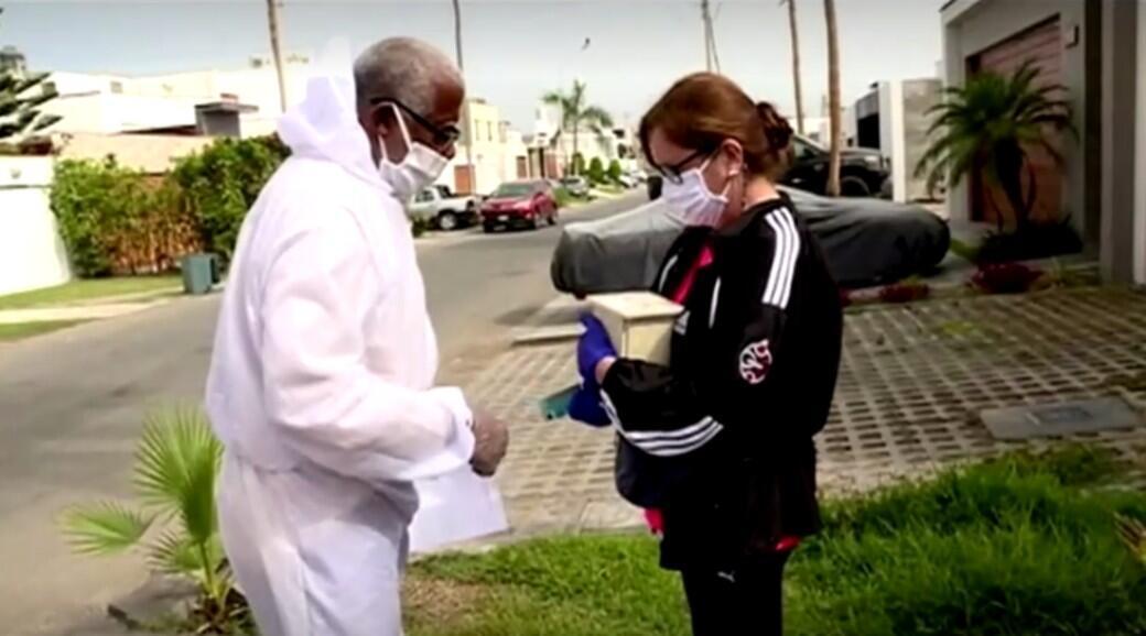 Héctor Orellanqui, trabajador de un crematorio entrega las cenizas de un fallecido por Covid-19, a una de sus familiares, en Lima, Perú, el 20 de mayo de 2020.