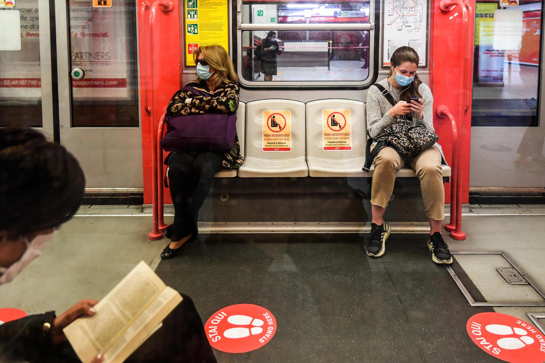 Dos mujeres con mascarilla viajan con dos asientos de espacio entre ellas en un vagón del metro de Milán, el 4 de mayo de 2020 en la estación de Cardona de la ciudad italiana.