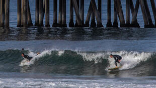 Surfers catch a wave in Huntington Beach, California on May 2