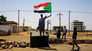 Un manifestante sudanés sostiene una bandera nacional mientras se para en una barricada a lo largo de una calle, exigiendo que el Consejo Militar de Transición del país entregue el poder a los civiles, en Jartum, Sudán, el 5 de junio de 2019.