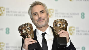 El director mexicano, Alfonso Cuarón, posando con dos premios Bafta a Mejor Película y Mejor director, Londres, Inglaterra, 10 de febrero de 2019.