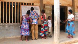 Les électeurs examinent une liste électorale à l'extérieur d'un bureau de vote dans le quartier de Be à Lomé le 20 décembre 2018 lors de la procédure de vote pour les élections législatives.
