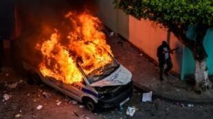 مسلح مقنع يسير قرب سيارة للشرطة تشتعل فيها النيران خلال صدامات بين قوات الأمن ومحتجين في الجزائر العاصمة في 12 أبريل 2019