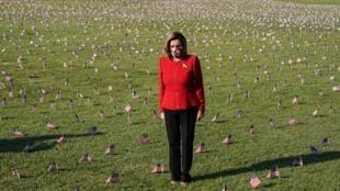 La presidenta de la Cámara de Representantes de EE. UU., Nancy Pelosi, se encuentra entre 20.000 banderas estadounidenses que representan las 200.000 vidas perdidas en el país por la pandemia, en el National Mall en Washington, EE. UU., el 22 de septiembre de 2020.