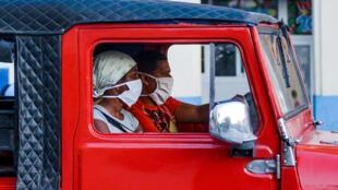 Afrocubanos llevan máscaras faciales como medida preventiva contra la propagación del coronavirus, COVID-19, mientras recorren en coche las calles de La Habana, el 13 de julio de 2020.
