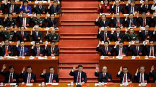El presidente Xi Jinping y los delegados del PCC levantan sus manos durante una votación en la sesión de cierre del Congreso partidario en Beijing, el 24 de octubre de 2017.
