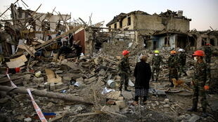Search and rescue teams work on a blast site hit by a rocket in the city of Ganja, Azerbaijan, on October 17, 2020.