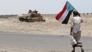 Un combattant formé par les Émirats arabes unis agite un drapeau séparatiste alors qu'il se dirige vers un tank à l'entrée Est d'Aden depuis la province d'Abyan, dans le sud du Yémen, le 30 août 2019.