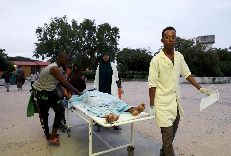 Des ambulanciers et des civils transportent un blessé après une explosion et une fusillade dans l'hôtel Elite, à Mogadiscio, en Somalie, le 16 août 2020.