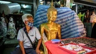 A vendor wearing a face mask against the spread of the coronavirus sits beside a Buddha statue as he waits for customers at an amulet market in Bangkok