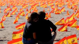 Una pareja se sienta frente a miles de banderas de España que representan a los fallecidos por el coronavirus, el 4 de octubre de 2020 en una playa de Valencia