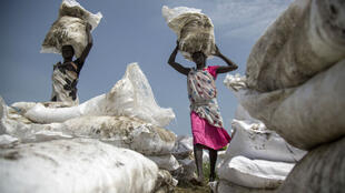 Women carry sacks of food airdropped by the World Food Programme and distributed by the NGO Oxfam in Padding, near Lankien, Jonglei, South Sudan, on July 3, 2017.