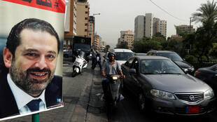 Los automóviles pasan junto a un cartel de Saad Hariri, que ha renunciado como primer ministro dee Líbano, en Beirut, el 13 de noviembre de 2017.