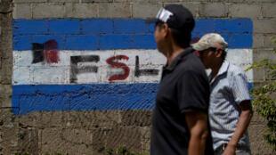 Dos hombres caminan frente a una pintada de la bandera de Nicaragua con las siglas del partido de gobierno FSLN este 10 de marzo en un barrio de Managua