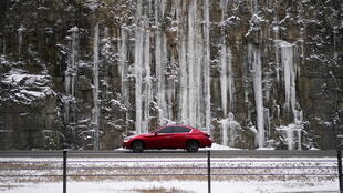 A motorist drives past a rock wall covered with ice on Interstate 71 as snow begins to fall in Louisville, Kentucky, U.S., February 15, 2021.