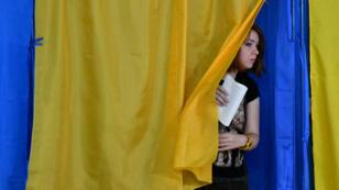 Une électrice s'apprête à voter pour les élections législatives anticipées en Ukraine, le 21 juillet 2019, à Kiev.