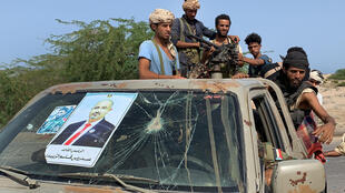 Fighters loyal to Yemen's Southern Transitional Council (STC) separatists stand in the back of a truck bearing the portrait of STC Chief Aidarus al-Zubaidi at the frontline of clashes with pro-government forces for control of Zinjibar