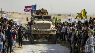 Des Kurdes manifestent autour d'un véhicule militaire américain pour dénoncer le retrait des troupes américaines et l'offensive turque imminente, le 6 octobre 2019.