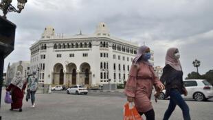 جزائريات يضعن أقنعة واقية يمرن أمام مبنى مكتب البريد الكبير في وسط العاصمة الجزائر، في 12 آب/أغسطس 2020