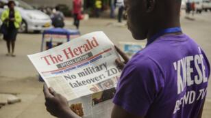 أحد سكان هراري يقرأ الأخبار غداة سيطرة الجيش على المدينة