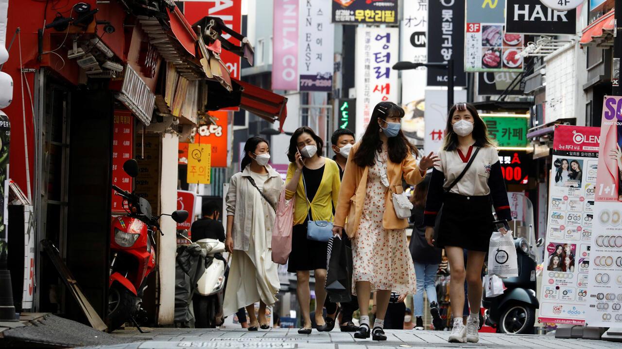 Personas con máscaras caminan en el distrito comercial de Myeongdong en medio de las medidas de distanciamiento social para evitar la propagación de la enfermedad por coronavirus, en Seúl, Corea del Sur, el 28 de mayo de 2020.