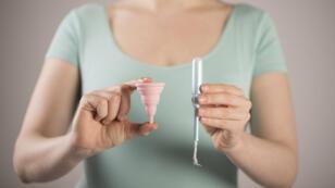 Une femme tenant une coupe menstruelle et un tampon.