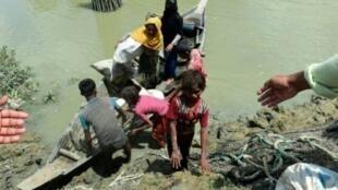 سكان في بنغلادش يساعدون اللاجئين الروهينغا على النزول من قارب في 11 أيلول/سبتمبر.