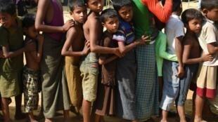 Des enfants font la queue pour recevoir des vivres dans un camp de réfugiés pour Rohingya au Bangladesh, le 22 septembre 2017.
