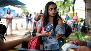 Una venezolana muestra su pasaporte y carta de identidad en el punto de control fronterizo de Pacaraima, en el estado de Roraima, Brasil. 16 de noviembre, 2017.