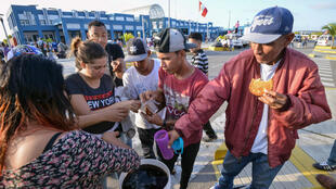 Des réfugiés vénézuéliens reçoivent la nourriture de bénévoles religieux alors qu'ils attendent une autorisation pour entrer au Pérou, à Tumbes, le 23 août 2018.