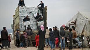 توزيع مساعدات إنسانية في شمال غرب سوريا قرب الحدود مع تركيا في 21 شباط/فبراير 2020