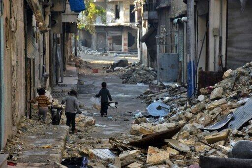 أطفال يعبرون في أحد أحياء حلب المدمرة في 18 كانون الثاني/يناير 2017