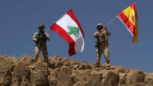 Des soldats libanais agitent leur drapeau national et celui de l'Espagne, en hommage aux victimes des attentats de Catalogne, le 19 août 2017.