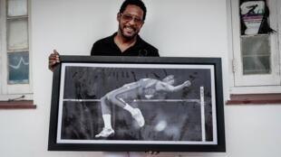 Esta imagen de archivo, tomada en julio de 2018, muestra al exatleta cubano Javier Sotomayor, plusmarquista mundial en salto de altura, con una imagen de sí mismo durante una entrevista con la AFP en La Habana