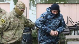 Un agent russe du FSB escorte un marin ukrainien au tribunal à Simferopol (Crimée), le 27novembre2018.