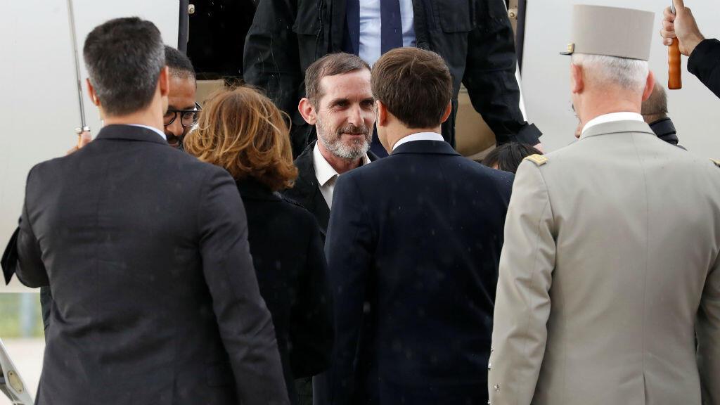 Los rehenes franceses liberados, Patrick Picque y Laurent Lassimouillas, mientras eran recibidos por el presidente francés, Emmanuel Macron, y la ministra de Defensa francesa, Florence Parly, a su llegada al aeropuerto de Villacoublay, el 11 de mayo de 2019.