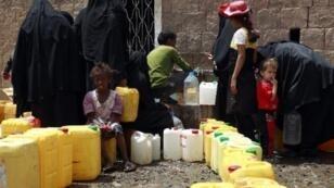 يمنيون يملأون أوعيتهم بالماء من صنبور عام في صنعاء في 9 أيار/مايو 2015