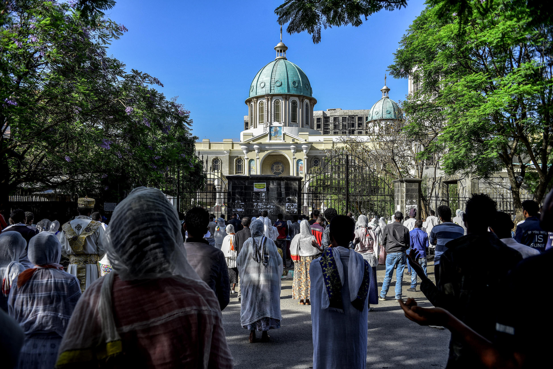 مسيحيون أرثوذكس يصلون خارج كاتدرائية مقفلة بسبب فيروس كورونا المستجد في أديس أبابا في 5 نيسان/أبريل 2020.