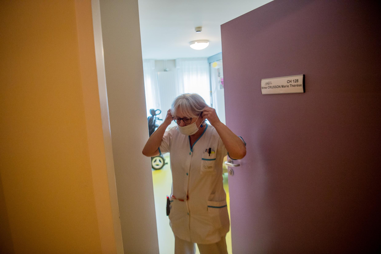 Une infirmière met un masque de protection avant de s'occuper d'un pensionnaire malade, le 4 mars 2020 dans un EHPAD de Brest