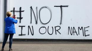 """""""#Pas en notre nom"""", graffiti inscrit dans le quartier Creggan de Londonderry (Irlande du Nord), le 20avril2019, au lendemain de la mort de la journaliste Lyra McKee."""