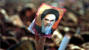 Un hombre iraní sostiene un retrato del fallecido líder y fundador de la revolución islámica, el Ayatollah Jomeini durante un mitin en la plaza Azadi en Teherán, el 11 de febrero de 1999.