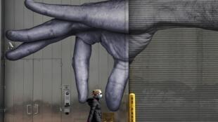 شابة تضع كمامة أثناء مرورها أمام مبنى عليه جدارية ليد رجل في وسط مدينة نيويورك في 22 نيسان/أبريل 2022.