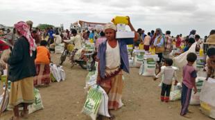 نازحون جراء النزاع في اليمن يتلقون مساعدات غذائية مقدمة من منظمة خيرية كويتية في قرية حيس قرب الحددية في 22 شباط/فبراير 2021