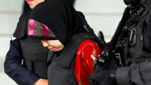 La indonesia Siti Aisyah, quien está siendo juzgada por el asesinato de Kim Jong-nam, el hermano líder norcoreano, Kim Jong-un, es escoltada de camino al Tribunal Superior de Shah Alam, a las afueras de Kuala Lumpur, Malasia, el 16 de agosto de 2018.