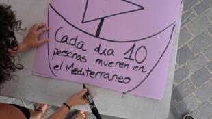 Una manifestante en España escribe un mensaje que muestra la crisis migratoria y humana que se vive en Europa. 29 de julio de 2018.