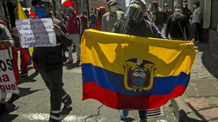 A protester holds an Ecuadorean flag during a demonstration in Quito against wage and budget cuts imposed by the government to tackle the coronavirus pandemic