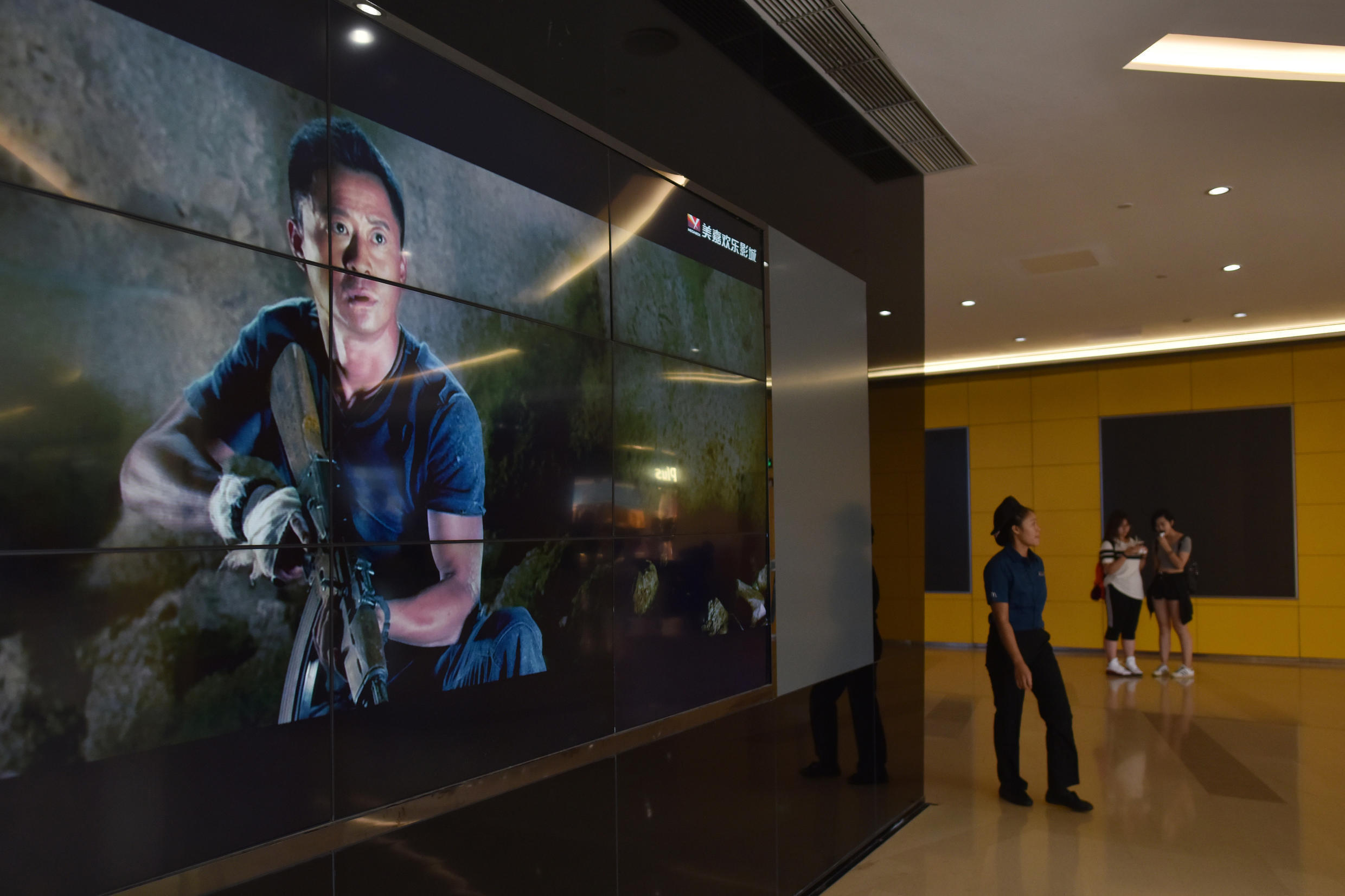 """Video screen showing scenes from the movie """" Wolf Warrior 2"""" in Beijing in August 2017."""