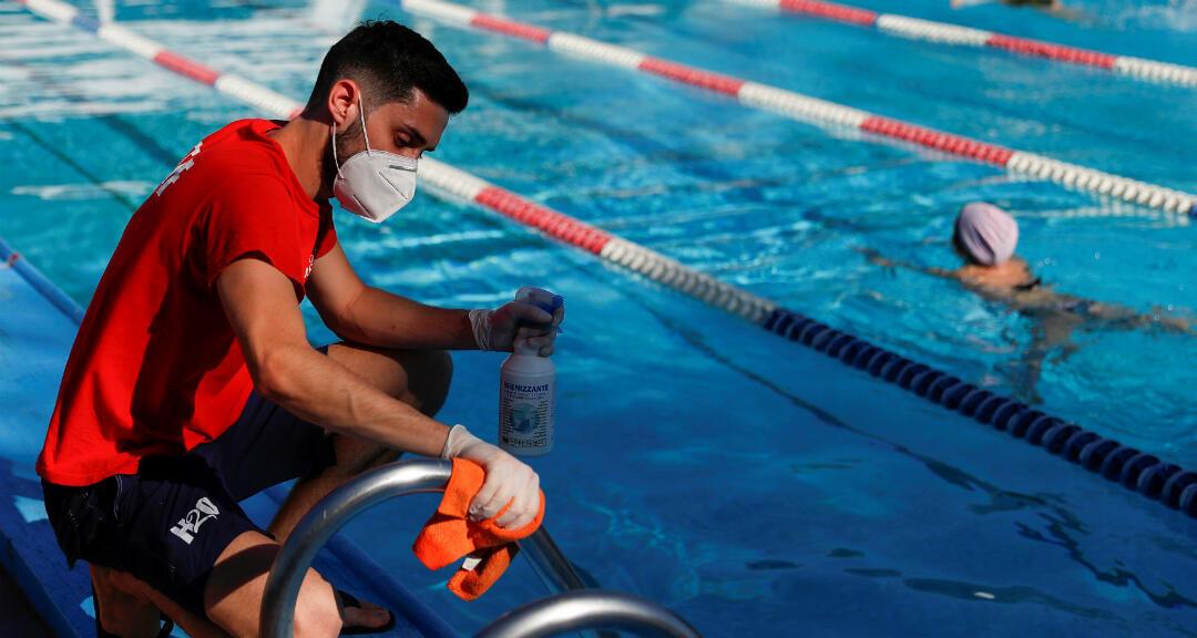 Un trabajador de una piscina que lleva mascarilla desinfecta un pasamanos en el primer día de apertura tras el bloqueo por el Covid-19. Roma, Italia, el 25 de mayo de 2020.