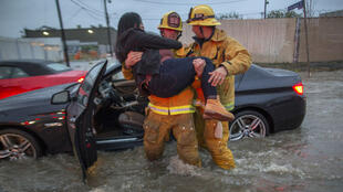A firefighter carries a woman from her car after it was caught in street flooding as a powerful storm moves across Southern California on February 17, 2017 in Sun Valley, California.