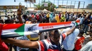 متظاهر سوداني يرفع يافطة أمام مقر الاعتصام في الخرطوم في 14 مايو/أيار 2019.